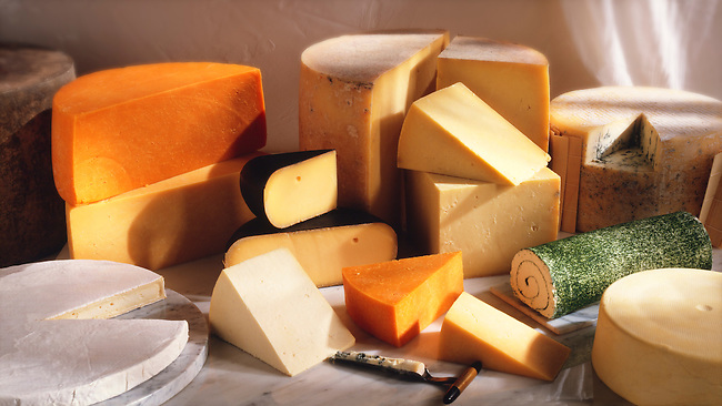 British cheese shop photo. A selection of  Cheeses, From left, Red Leicester cheese on top of Leicester cheese, in the black wax, Dutch cheese, then a truckle of farmhouse mature cheddar cheese then a stilton cheese with a French Roule in front. Funky Stock photos.