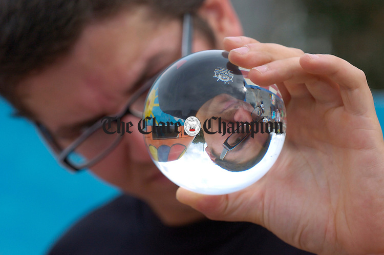 Paulo, a contact juggler with the Galway Circus Project is seen in his own glass ball while performing during the street carnival in Ennis market on Sunday. Photograph by John Kelly.