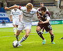 Raith Rovers' Jason Thomson holds off Hearts' Jason Holt.