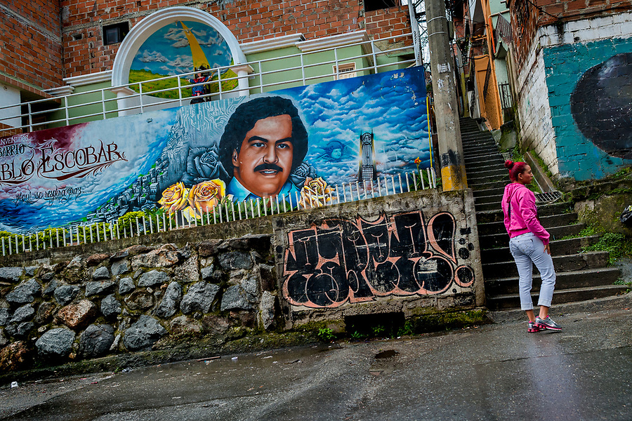 """A Colombian woman walks along a large mural artwork, depicting the drug lord Pablo Escobar, painted on the wall in the Pablo Escobar neighborhood in Medellín, Colombia, 30 November 2017. Twenty five years after Pablo Escobar's death, the legacy of the Medellín Cartel leader is alive and flourishing. Although many Colombians who lived through the decades of drug wars, assassinations, kidnappings, reject Pablo Escobar's cult and his celebrity status, there is a significant number of Colombians who admire him, worshipping the questionable """"Robin Hood"""" image he had. Moreover, in the recent years, the popular """"Narcos"""" TV series has inspired thousands of tourists to visit Medellín, creating a booming business for many but causing a controversial rise of narco-tourism."""