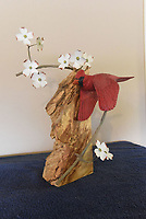 NWA Democrat-Gazette/FLIP PUTTHOFF<br />A cardinal flies among dogwood blossoms Aug. 11 2017 in this carving.