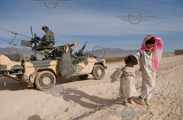 Afghan children shy away from a military vehicle, manned by Dutch ISAF (the International Security Assistance Force) soldiers, on the main supply route (MSR) from Camp Holland to the Chora Valley. ISAF is a peacekeeping mission affiliated to the United Nations (UN) and NATO. .