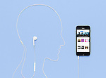Man head outline made by a headphones cord plugged into iPhone 5s phone with iTunes music store on its display. Creative concept on blue background.