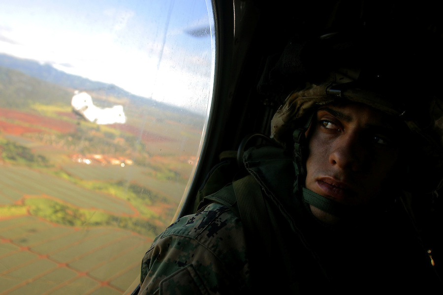 PFC Joey Trinidad (Weapons Platoon, Charlie Co. 1/4 Marines) watches the vermillion soil of the Hawaiian landscape slide by the window of the helicopter carrying Charlie to two days of training at Schofield Army Barracks ahead of a scheduled seven month deployment to Iraq.