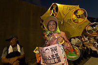 A woman holds an umbrella decorated with anti nuclear symbols as protestors call for the abolition of nuclear power in the weekly Friday night protests outside the Prime Minister's office and national diet building in Tokyo, Japan.Friday September 7th 2012