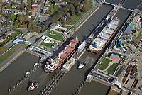 Nord Ostseekanal Schleuse Brunsbuettell: EUROPA, DEUTSCHLAND, SCHLESWIG-HOLSTEIN, BRUNSBUETTEL , (EUROPE, GERMANY), 19.10.2018: Schleuse Nord-Ostseekanal von Brunsbuettel. Der Nord-Ostsee-Kanal (NOK; internationale Bezeichnung: Kiel Canal) verbindet die Nordsee (Elbmuendung) mit der Ostsee (Kieler Foerde). Diese Bundeswasserstra&szlig;e ist nach Anzahl der Schiffe die meistbefahrene kuenstliche Wasserstra&szlig;e der Welt.<br /> Der Kanal durchquert auf knapp 100 km das deutsche Bundesland Schleswig-Holstein von Brunsbuettel bis Kiel-Holtenau und erspart den etwa 900 km laengeren Weg um die Nordspitze Daenemarks durch Skagerrak und Kattegat.<br /> Die erste kuenstliche Wasserstra&szlig;e zwischen Nord- und Ostsee war der 1784 in Betrieb genommene und 1853 in Eiderkanal umbenannte Schleswig-Holsteinische Canal. Der heutige Nord-Ostsee-Kanal wurde 1895 als Kaiser-Wilhelm-Kanal eroeffnet und trug diesen Namen bis 1948. Zwei Frachtschiffe fahren unter Schlepperhilfe in die Schleuse.