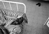Asmara, Eritrea.November 2002.Birhan Aim Hospital  (Light to the Eye Hospital)..A patient lays still with his head hanging from the bed after eye drops are place to prevent infection. Following the surgery the patients must take the medication regularly for several days to avoid infection as their sight steadily improves.