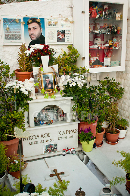 Tomb of a young man with flowers, plants, objects from his life in a cemetery, Fira, Santorini (Thira), Greece