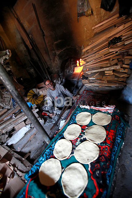 A Palestinian baker prepares loaves of bread at his traditional bakery in the holy month of Ramadan in Gaza City on Aug. 15, 2011. Muslims around the world abstain from eating, drinking and conducting sexual relations from sunrise to sunset during Ramadan, the holiest month in the Islamic calendar. Photo by Ashraf Amra