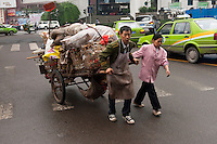 Daytime landscape view of a man and a woman pulling a hand cart loaded with burlap bags on Hui Long Jie in Jiāngyáng Qū of the Lúzhōu Prefecture City in Sichuan Province.  © LAN