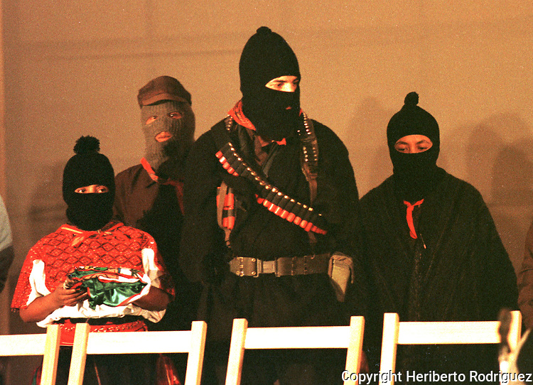 Zapatista Comandante Ramona craddles a folded Mexican flag next to Subcomandante Marcos during the beginning of the peace talks between Mexican government envoys and Zapatista comandantes at the San Cristobal Las Casas' Cathedral, February 21, 1994.  The Zapatista National Liberation Army (EZLN) launched an uprising in January 1st, 1994 demanding Indian rights and opposing to the North American Free Trade Agrreement (NAFTA) signed by Carlos Salinas de Gortari with US and Canada governments. Photo by Heriberto Rodriguez