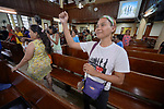 Methche Bayan raises her arm as she sings during worship at Knox United Methodist Church in Manila, Philippines. The service is part of a weekday program where the church opens up to poor people in the neighborhood, offering showers, food, fellowship, and an opportunity to worship together.