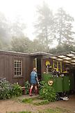 USA, California, Big Sur, Esalen, Kat enters a garden shed to retrieve some tools in the Buddha Garden