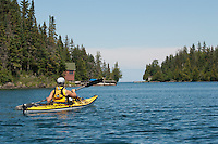 A kayaker paddles past old boathouses at Tobin Harbor at Isle Royale National Park.