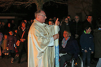 Pfarrer Christof Mulach hat mit dem Osterfeuer die Osterkerze entzündet und trägt sie in die Kirche