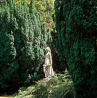 A classical figure stands between two yew trees in the gardens at Newby Hall