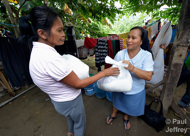 After the passage of Typhoon Bopha, Sister Maria Famita Somogod, a member of the Missionary Sisters of Mary (right) delivers a food parcel to Gloria Riez, who was displaced by the storm in Iligan, on the southern Philippines island of Mindanao. Somogod is the Northern Mindanao coordinator of the Rural Missionaries of the Philippines.