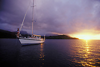 Woman standing on bow of sailing yacht with sunset in background at anchor in Hanalei Bay, Kauai, Hawaii