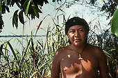 Amazon, Brazil. Davi Kopenawa Yanomami standing beside a river.