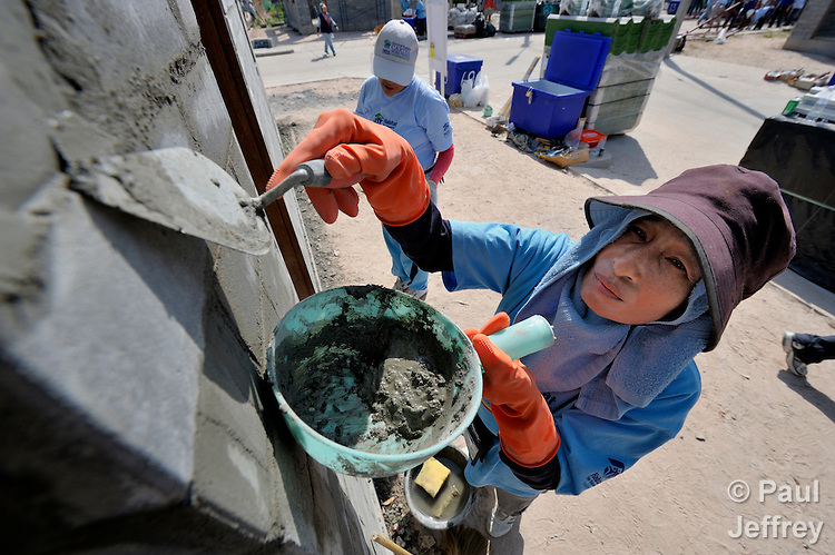 Wanida Sotkrang, a 50-year old woman living with HIV in the city of Chiang Mai in northern Thailand, works on her new home during a massive Habitat for Humanity home construction event that included former US President Jimmy Carter.