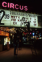 Workers change the marquee of the Circus Cinema showing XXX rated films in Times Square in March 1987. (© Richard B. Levine)