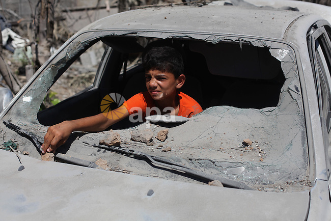 A Palestinian boy sits inside the remains of a car that witnesses said was destroyed in an Israeli offensive, after a ceasefire was declared in the Shejaia neighbourhood, east of Gaza City. September 6, 2014. Calm returned to the coastal enclave in a August 26 ceasefire, and Gazans were gradually starting to rebuild their lives after a bloody and destructive 50-day war, the deadliest for years. Photo by Ashraf Amra