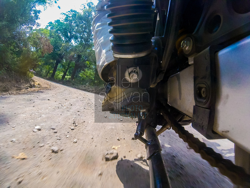 Low angle from left swingarm of motorcycle looking forward during a ride. Rider's left boot is seen as well as terrain being ridden. Shot near Antigua, Guatemala.