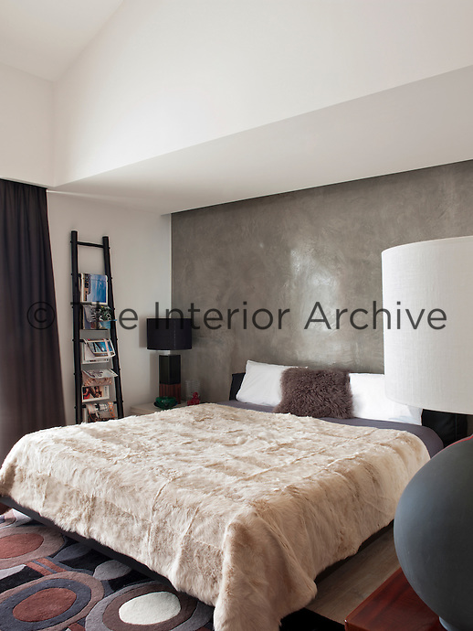 A black bamboo ladder magazine rack in the master bedroom with polished concrete back wall and fur bedcover