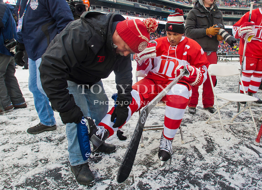 31 December 2013: Red Wings ice manager Al Sobotka helps former forward and captain Steve Yzerman (19) with putting on his skate blade guards, after warmups before the Toronto Maple Leafs v Detroit Red Wings Alumni Showdown hockey game, at Comerica Park, in Detroit, MI.