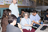 Megan Gall, of Washington, D.C., (in blue shirt with red pants) speaks to participants during the Metric Geometry and Gerrymandering Group (MGGG) hackathon at the Data Lab in the Tisch Library at Tufts University in Medford, Massachusetts, USA, on Thurs., Aug. 10, 2017. Gall is a Social Scientist at the national Lawyers' Committee for Civil Rights Under Law. She is working on ways to routinize ecological inference statistics and then visualize that as a way to teach others what ecological inference means and does. Ecological inference is a way of using aggregate data, such as racial or ethic information, to infer what an individual might have done, in this case during a vote. Gall, and others investigating gerrymandering, use ecological inference as a way to identify districts that may have racially polarized voting. The hackathon is part of the first in a series of Geometry of Redistricting workshops put on by the MGGG. Academics, Geographic Information Systems (GIS) professionals, and legal professionals worked together to build tools useful in analyzing voting district data around the country.