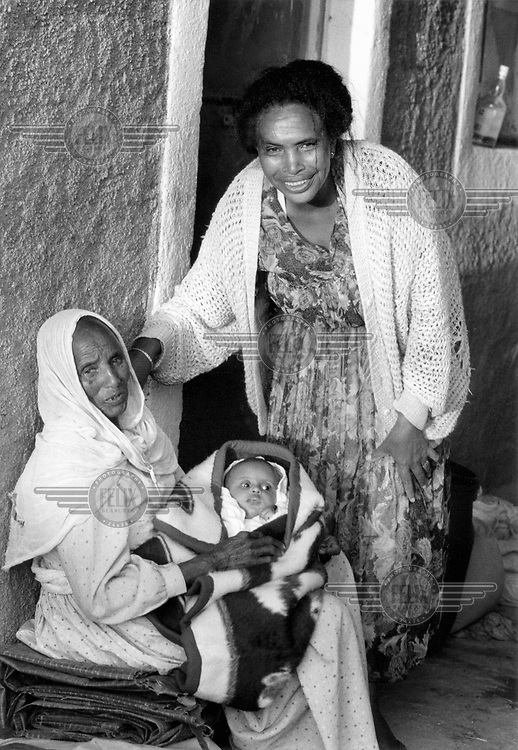 © Heldur Netocny / Panos Pictures..Korbaria, ERITREA..Three generations of one family: great-grandmother, grandmother and child.