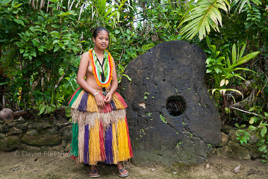 This young girl in a traditional outfit is pictured in front of a peice of stone money in the village of Kadai, on the island of Yap, Micronesia.