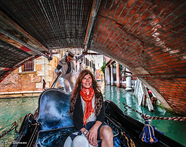 Venice: A visitor enjoying a gondola ride, glides under a colorful bridge in Venice, Italy..