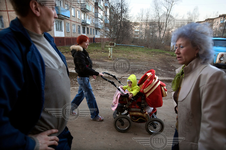 A young woman pushes a baby in a pram in the town of Ivanovo.