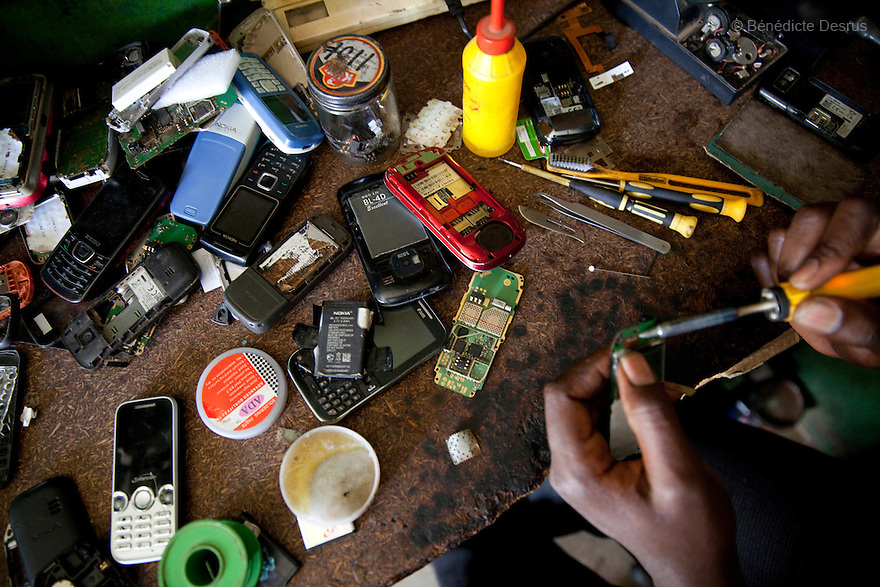 A Kenyan man repairs second-hand mobile phones at his shop in Nairobi slum on March 22, 2013. (Photo by Benedicte Desrus)