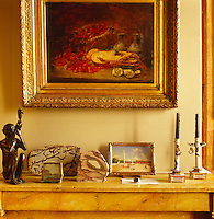 In the study the mantelpiece displays an interesting collection of objects, paintings and small sculptures beneath a gilt-framed 19th century painting