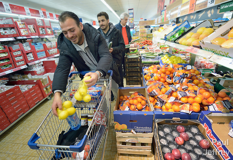Mohammed Anini loads groceries in his cart in a store in Messstetten, Germany. A refugee from Damascus, Syria, he has applied for asylum in Germany and is awaiting word on the government's decision. Meanwhile, he lives in a former army barracks in Messstetten. Behind him is Anas Sriwa, also a Syrian refugee.