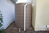 865 gallon rain barrel next to Green home that is off the grid. Solar power and a rainwater harvesting system supply all the energy and water for this home in Los Angeles, California, USA