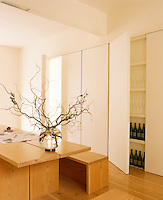 An open door in the wall of flush cupboards in this minimal dining room reveals shelves for storing bottles of wine and water