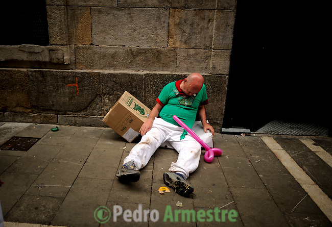 A drunk man sleeps in Estafeta street during the San Fermin festival, on July 10, 2012, in the Northern Spanish city of Pamplona. The festival is a symbol of Spanish culture that attracts thousands of tourists to watch the bull runs despite heavy condemnation from animal rights groups. (c) Pedro ARMESTRE