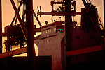Panamax container ship framed by container cranes at dusk, Port of Seattle, Washington State, Pacific Rim Trade..