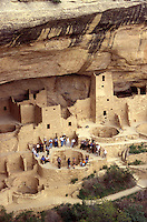 Tourists and guide standing around a kiva at Cliff Palace ruins, Mesa Verde National Park, Colorado, USA