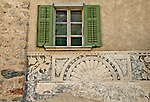 Window with green shudders and a fresco below, in the small town of Viscoprano, a Swiss town in the Bregaglia Valley which dates back to 1096