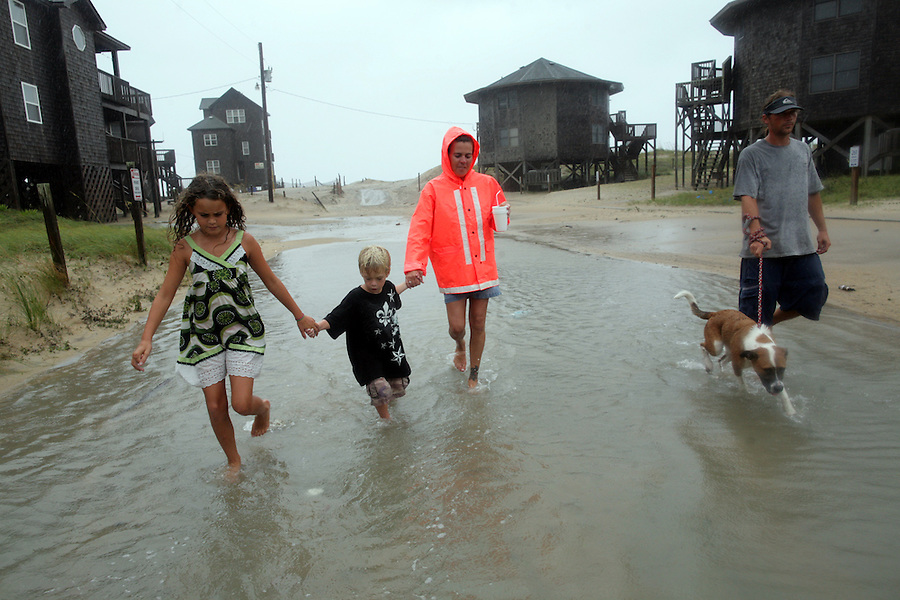 Lexus Meekins,  9, right, and her aunt Jessica Meekins, center, help Lexus' brother Freeman Meekins, 5, walk along a flooded street from the beach with Jessica Meekins' fiance Eric Hissey, right, and his dog Bella, as Hurricane Irene continued to bring wind and rain to Buxton, NC, on the Outer Banks on Saturday, Aug. 27, 2011.  The adults took the kids to see the beach because they were getting cabin fever in the hotel during the long storm.  The sand blast from the high winds was too much for them, and they left after only a minute.  Photo by Ted Richardson