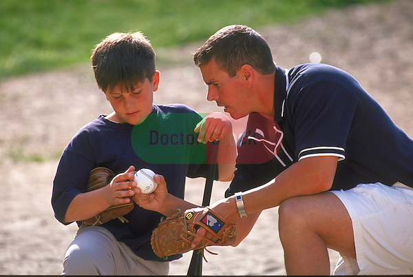 father teaching boy to throw baseball