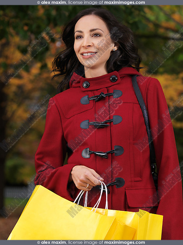Happy young beautiful woman in a red coat walking with shopping bags in her hand
