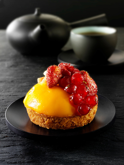 A modern fruit cake with redcurrants, wild strawberries, blacberry and creme patisserie in a light sponge case Traditionl black Japanese tea setting