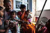 Caretakers and families feed RUTF to children at the government health centre in  Hanuman Nagar, Saptari, Nepal.