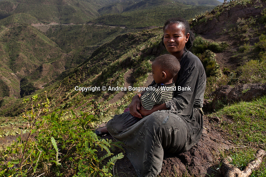 Ethiopia, Tigray region, Rayazebo District. Woman sitting in front of a new terraced land, part of the World Bank funded Sustainable Land Management Program. The community terraced the land first to retain the water then planted local tree seedling.