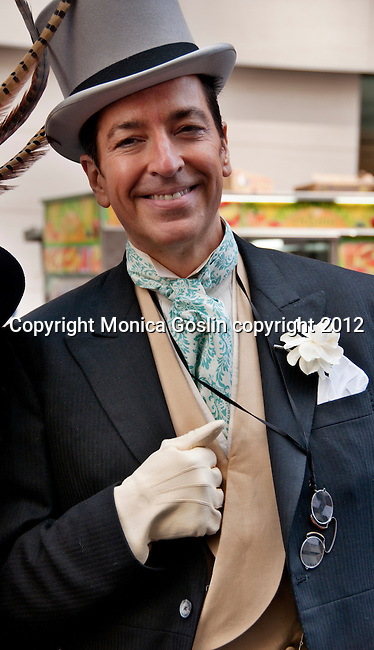 A man in the New York City Easter Parade wearing a gray suit, a top hat, small vintage eye glasses, white gloves, and a fancy tie